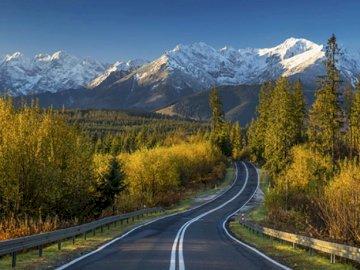 Krajobraz górski - szosa - Krajobraz górki, zachód słońca - szosa. Pociąg na torze kolejowym z górą w tle.