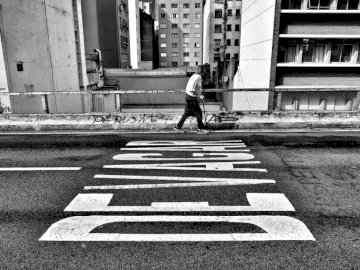 Slow people - Gray scale photography of person walking beside pave road. São Paulo. A person walking down a stree