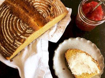 Handwerkerbrot mit Butter und - Braunes Gebäck auf weißem Papier. Eine Nahaufnahme von Essen auf einem Tisch.