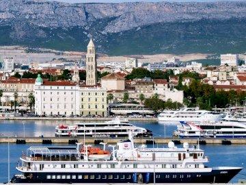 Zdjęcie z promu Split - Biały statek wycieczkowy na morzu blisko miasto budynków podczas dnia. Duży statek w akwenie.