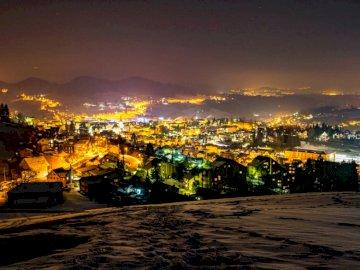 Herisau nocą ze wzgórza - Oświetlone budynki i domy w nocy. Zachód słońca nad akwenem z miastem w tle.