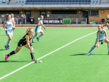 Hockey femminile - Donna che indossa maglia nera che gioca sul campo. Australia, Melbourne. Un gruppo di persone che gi