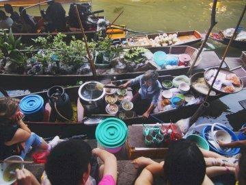 Rynek rzeczny w Tajlandii - Płaskie zdjęcie pływającego rynku. Grupa ludzi stojących przed tłumem.