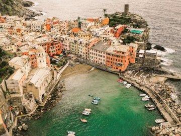 Cinque Terre, Italie - Photographie de vue aérienne de bateau cuddy sur le plan d'eau entre les bâtiments. Un gro