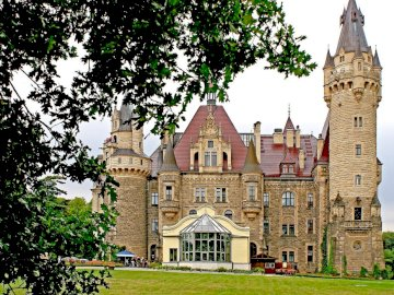 Moszna Castle Poland - around Opole - 99 towers and 365 rooms. A church with a clock tower in front of a house.