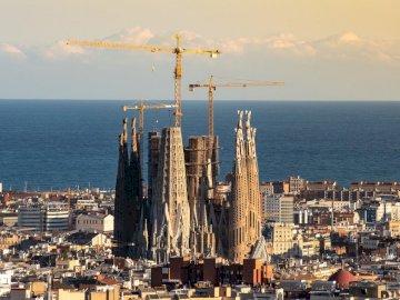 Sagrada Familia - Sagrada Familia w Barcelonie. Duży zbiornik wodny z miastem w tle.