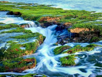 Fast river current - green and blue --------------------. A large waterfall over a body of water.