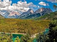 Vackert berg - Vackert berg med bäck och skog. En närbild av en sluttning med träd och ett berg i bakgrunden.