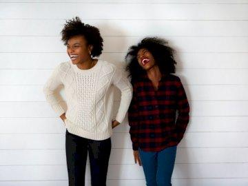 Esta imagen te es presentada - Dos mujeres sonriendo. Nueva York. Un hombre y una mujer de pie en una habitación.