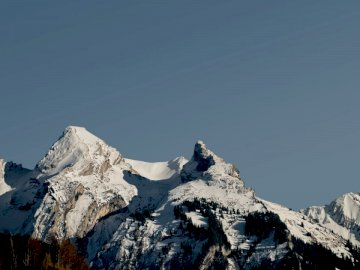 Last snow - Snow covered mountain during daytime. Switzerland. A man flying through the air on a snow covered mo