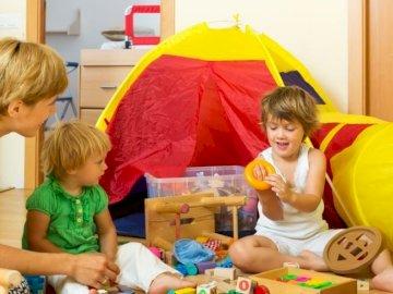 mama bawi się z dziećmi - mama bawi się z dziećmi w ich pokoju. Małe dziecko siedzi na stole.