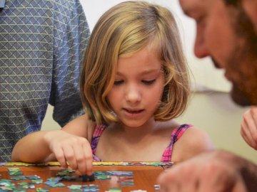 Bleib zu Hause Rätselzeit - Mädchen im blauen und weißen Tupfen-Trägershirt, das auf braunem Holztisch spielt. Florida. Ein M