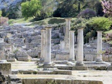 Archäologische Stätte von Glanum - Archäologische Stätte von Glanum. Ein Steingebäude mit einer Felswand.
