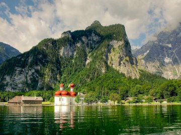 Panorama of Konigssee - Bavaria - alpine landscape. A small boat in a body of water with a mountain in the background.