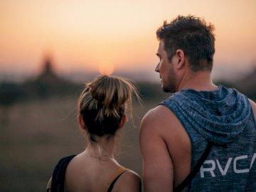 J'étais donc au coucher du soleil - Photographie de mise au point sélective de l'homme debout à côté de la femme tout en reg