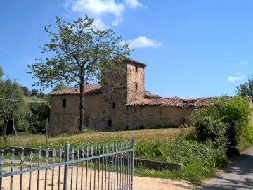 włoska prowincja - urocze miasteczko -północne Włochy. Duży ceglany budynek z trawą przed ogrodzeniem.