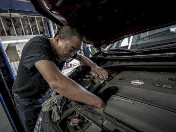 mecánico - el mecánico repara el auto. Un hombre sentado en un auto.