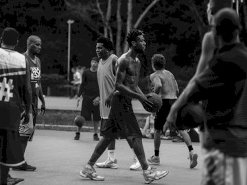 Outdoor basketball game - Grayscale photo of people playing basketball. A group of people standing on a basketball court.