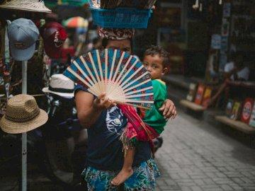 Cette femme vendait des fans - Femme portant un bébé cachant son visage à l'aide d'un ventilateur à main.
