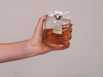 Chanel Gabrielle with Ribbon - Person holding clear glass perfume bottle. Austria. A hand holding a bottle.