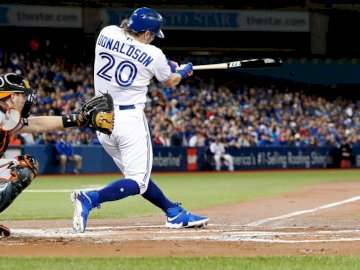 Baseball - Toronto Blue Jays during the game. A baseball player swinging a bat at a ball.