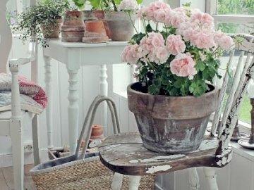 kwiaty na werandzie - Kwiaty i stare krzesło z kwiatami na werandzie. Wazon z kwiatami na stole obok okna.