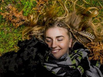 Cieszyć się naturą. - Uśmiechnięty kobiety lying on the beach na ziemi obok czarnego psa przy dniem. Sztokholm. Osoba po