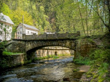 Stone bridge - fast river ---------------------------------------------. A bridge over a river in a forest.
