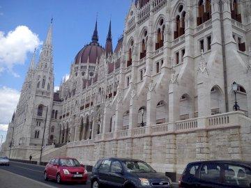 w Budapeszcie - Budynek Parlamentu, Budapeszt. Samochód zaparkowany przed dużym budynkiem.