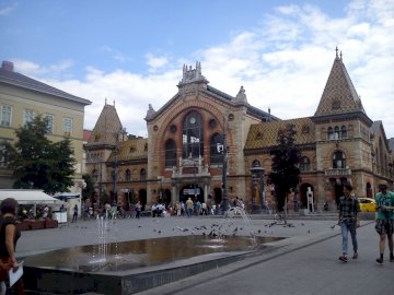 In Budapest - Great Market Hall in Budapest. A group of people walking in front of a building.