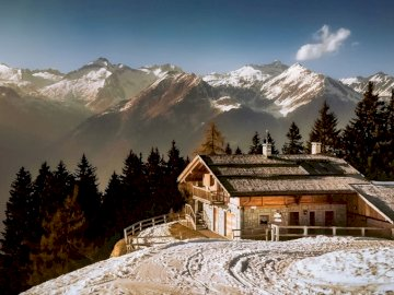 Alpine landscape - Italian Alps -----------------. A house covered in snow with a mountain in the background.
