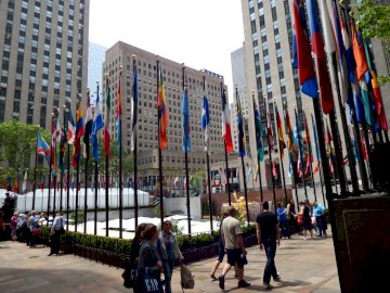 ROCKEFELLER CENTER, NY - EMBLEMATIC NY BUILDING. A group of people on a sidewalk in a city.