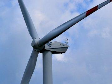 Éolienne dans le ciel bleu - Drapeau blanc et rouge sur poteau en métal blanc. Schleswig-Holstein, Allemagne. Un grand avion vol