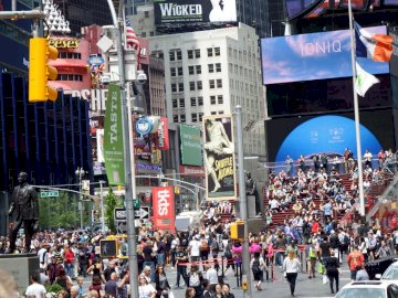 TIMES SQUARE, NEW YORK - COLORFUL AFTERNOON IN NEW YORK. A crowd of people walking on a city street.