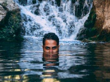 Sous l'eau - Homme dans l'eau près des montagnes Rocheuses pendant la journée. Un homme debout à côt�