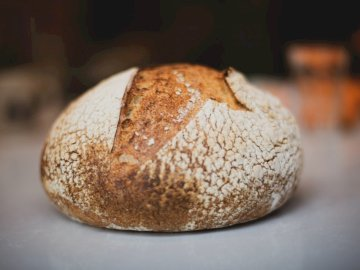 Chleb, jedzenie - Brown i biały chleb na bielu stole. Zbliżenie jedzenia.