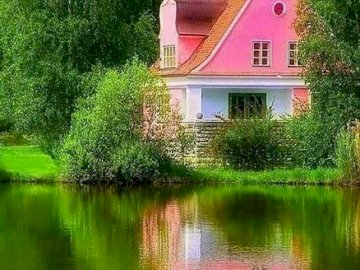 A pink house. - Jigsaw puzzle. Construction: a pink house. A body of water surrounded by trees.