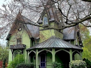 victorian hoisr - green victorian house. A small church in a garden.