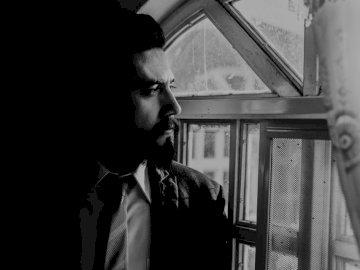 Mężczyzna czeka na kogoś. - Mężczyzna w czarnym garniturze, patrząc z okna. Guadalajara México. Mężczyzna w garniturze i k