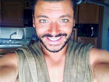Kev Adams - Puzzle na moim idolu. Kev Adams uśmiecha się do kamery.