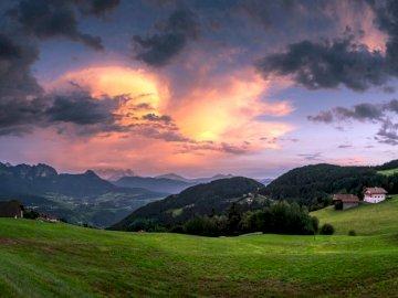 Folge meinem Instagram - Die Sonne ging über dem Horizont unter. Mainz, Deutschland. Ein großes grünes Feld mit einem Berg