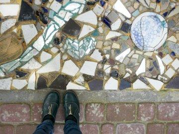 Gebrochene Keramikfragmente schmücken - Paar schwarze Schuhe. Weißrussland.