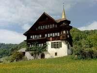 Türmlihaus (wieżowiec) z - Brązowy i biały betonowy dom w ciągu dnia. Herisau, Szwajcaria. Mała wieża zegarowa na środku