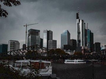 Frankfurt (Main), Niemcy | - Biała łódka blisko zawieszenie mosta pod nimbus chmurami. Berlin, Niemcy. Duży zbiornik wodny z