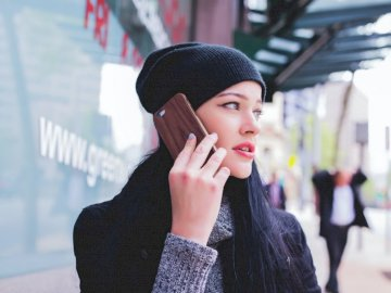 On a phone on a sidewalk - Woman wearing beanie with smartphone on ear. Sydney. A woman wearing a hat talking on a cell phone.