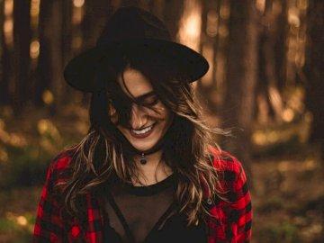 Lächeln in einem sonnigen Wald - Frau im Fedorahut, umgeben von Bäumen. Cianorte, PR - Brasilien. Eine Person, die einen Hut trägt.