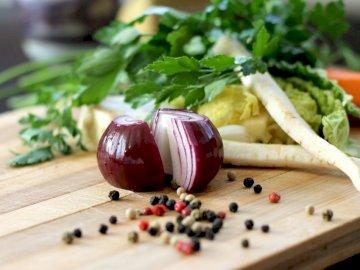 Składniki do gotowania - Czerwona cebula na brązowej drewnianej desce do krojenia. Zakończenie up jedzenie na stole.