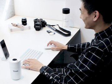 Designer desk. - Man using computer. Melbourne, Australia. A man sitting at a table with a laptop.