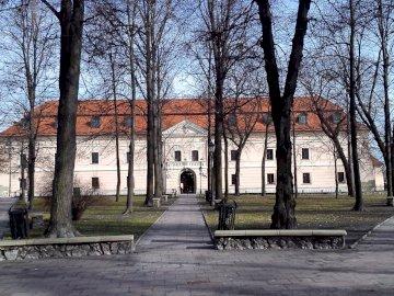 Zamek w Niepołomicach - Zamek Królewski w Niepołomicach. Pusta ławka w parku obok drzewa.