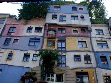 Hundertwasserhaus - Dom Hundertwassera w Wiedniu. Duży ceglany budynek z wieloma oknami z Hundertwasserhaus w tle.